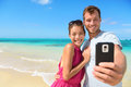 Beach vacation couple taking selfie on smartphone photograph using relaxing and having fun holding smart phone camera young Stock Images