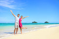 Beach vacation happy carefree couple arms raised winning with up showing happiness and fun on with pristine Royalty Free Stock Image