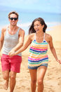 Beach vacation happy fun romantic couple running holding hands two cool trendy hipster people playful on summer travel holidays Stock Images