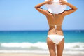 Beach vacation hot woman in sunhat and bikini beautiful standing with her arms raised to her head enjoying looking view of Stock Images