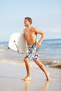 Beach water sports surfing man with body surfboard running happy during summer holidays vacation on tropical on sunny day Royalty Free Stock Photography