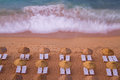 Beach waves coming towards with chairs and umbrellas Royalty Free Stock Photo
