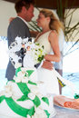 Beach wedding ceremony with cake in foreground background Royalty Free Stock Image