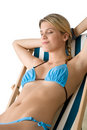 Beach - woman in bikini sitting on deck chair Royalty Free Stock Photo