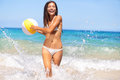 Beach woman having fun laughing enjoying sun in bikini running at with water spray splashing and a ball in her hands Stock Photography