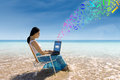Beach worker asian woman using a laptop for sending e mail on the Royalty Free Stock Image