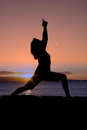Beach yoga at sunset a woman practicing silhouetted in the on the Royalty Free Stock Photo