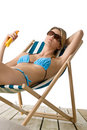 Beach - Young woman in bikini apply suntan lotion Stock Photo
