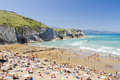 Beach of zumaia spain some people swimming in one the most beautiful and touristic beaches in basque country region on august in Stock Photography