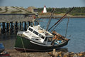 Beached Fishing trawlers with abandoned docks Stock Images
