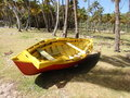 A beached rowboat in the caribbean hauled out at industry coconut plantation on bequia Royalty Free Stock Photos