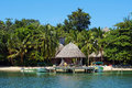 Beachfront eco resort with thatched hut over water and tropical vegetation caribbean sea bocas del toro panama Royalty Free Stock Photo