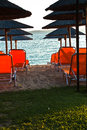 Beachscape with orange chairs, thatched sunshades and island in a background Royalty Free Stock Photo