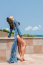 Beachwear holiday fashion vertical photo of a beautiful girl in blue and dress she is enjoying the sun and on a balcony Stock Photography