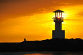 Beacon lighthouse searchlight beam through marine at sunset Stock Photos