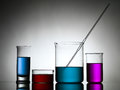 Beakers with dropper and colored liquid substances different sizes filled whith a in one against a gradient gray background laying Stock Image