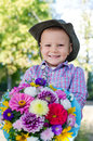 Beaming little boy with flowers for his mother Stock Photos