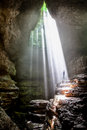 Beams of light fallling on a person in a cave Royalty Free Stock Photography