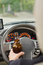 Bear bottle human hand holding a liquor while driving in a close up shot Royalty Free Stock Photography
