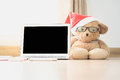 Bear doll wearing red hat sit beside laptop Royalty Free Stock Photo