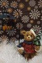 Bear holds a christmas tree and lantern