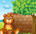 A bear with honey near a pile of bricks illustration Stock Photo