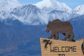 Bear sign welcoming visitors to haines junction yukon canada st elias mountains tower behind Stock Images
