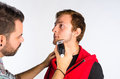 Beard trimming barber a with an electric razor Stock Images