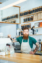 Bearded barista with tattooed hands in coffee shop white apron Royalty Free Stock Images