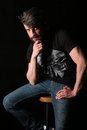 Bearded guy sitting on a bar stool and holding his chin . Close.up. Black