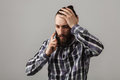 Bearded handsome sad man is talking by phone in blue squared shi Royalty Free Stock Photo