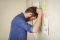 Bearded hipster frustrated at brainstorm wall in his office Royalty Free Stock Photography