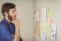 Bearded hipster looking at brainstorm wall in his office Stock Photo