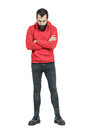 Bearded man with crossed arms in red hooded sweatshirt looking down full body length portrait isolated over white studio Royalty Free Stock Images
