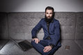 Bearded man dressed in suit and with laptop browsing internet;