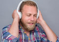 Bearded man in earphones listening to the music on grey blond model keeping his white with his eyes closed Stock Images