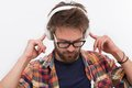 Bearded man in earphones profile of white glasses listening to the music and touching his Royalty Free Stock Image