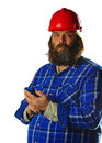 Bearded man in a hard hat with a smart phone Royalty Free Stock Image