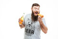 Bearded man holding bottle of beer and eating hot dog Royalty Free Stock Photo