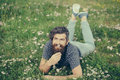 Bearded man laying on green grass smiling Royalty Free Stock Photo