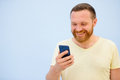 Bearded Man looking into the phone rejoices photo to advertise a lot of space under the text Royalty Free Stock Photo