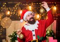 Bearded man Santa Claus decorating christmas tree with golden decorations. Winter decorations. Shimmering balls Royalty Free Stock Photo