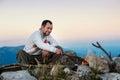 Bearded man sitting near fireplace on top of mountain