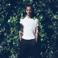 Bearded man with tattoo wearing blank white tshirt and black jeans.Green garden wall background. Square mockup