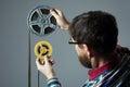 Bearded man watch two film reel 16mm Royalty Free Stock Photo
