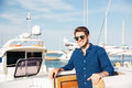 Bearded man wearing sunglasses and standing on a yacht Royalty Free Stock Photo