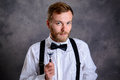 Bearded man in white shirt and bow tie showing shaver Royalty Free Stock Photo