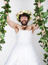 Bearded man in a woman's wedding dress on her naked body, clinging to the vine. grimacing and funny. on his head a Royalty Free Stock Photo