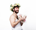 Bearded man in a woman`s wedding dress on her naked body, holding a flower. on his head a wreath of flowers. funny Royalty Free Stock Photo