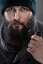 Bearded mezczyna dressed like a sailor he wears black cap and pipe in his mouth Stock Photo